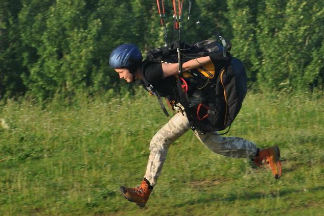 Взлет пилота парапланериста со склона